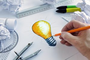 Designer drawing a light bulb, concept for brainstorming and inspiration